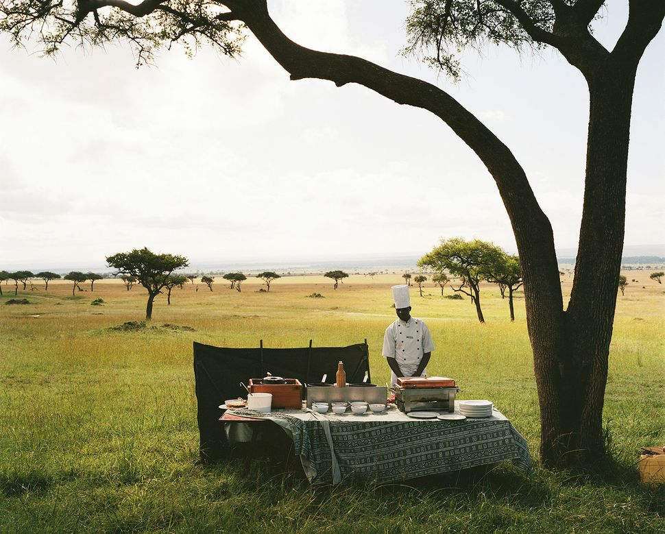 A chef from a nearby luxury lodge waits for his guests to arrive from a hot air balloon excursion before serving them champag