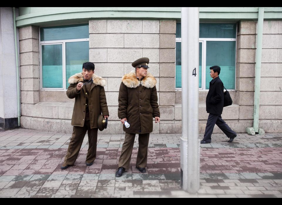 Two North Korean soldiers smoke cigarettes as a pedestrian walks past on a street corner in Pyongyang, North Korea.