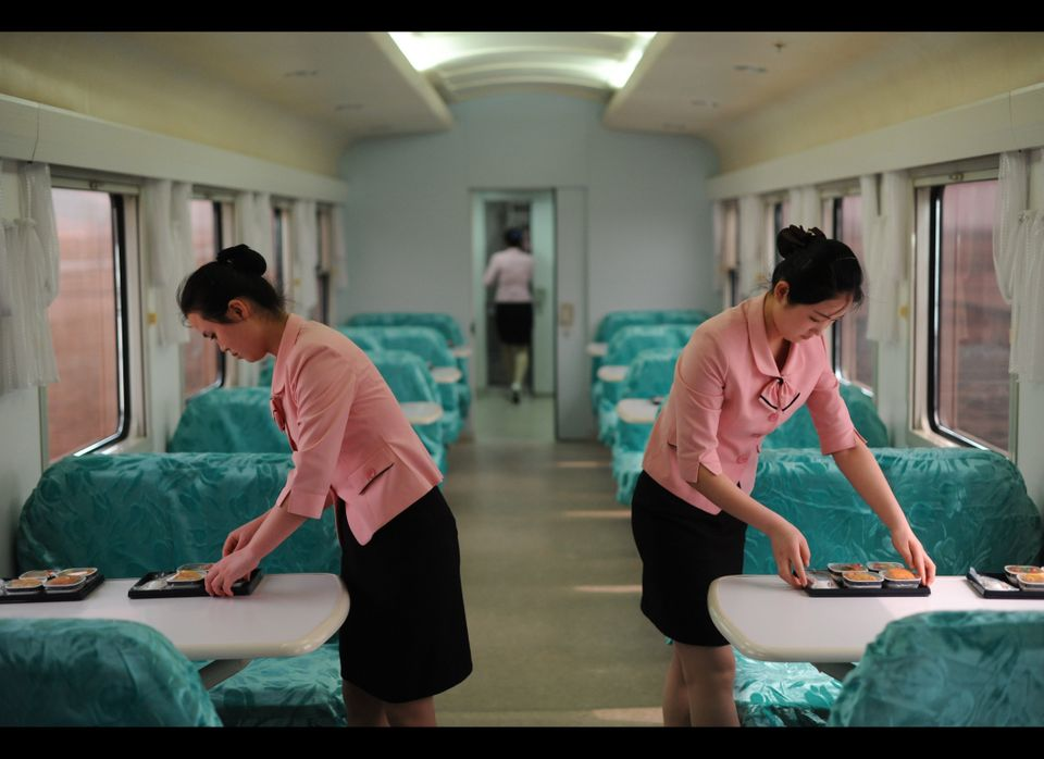 Two members of the crew serve food for journalists during the trip between Pyongyang and the North Phyongan Province on the w