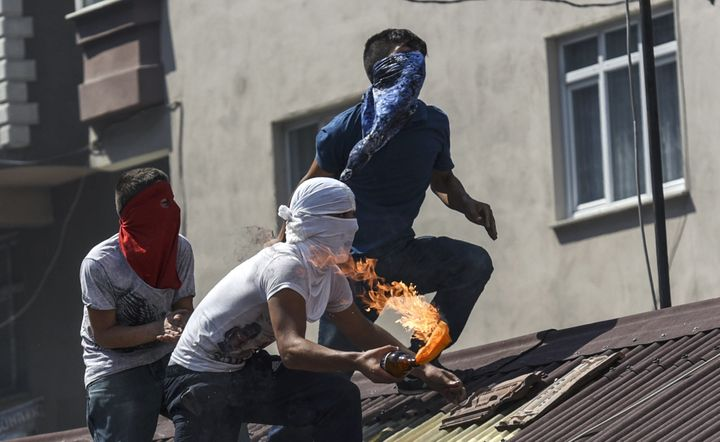 <span>Left-wing protesters&nbsp;prepare to throw a Molotov cocktail from a rooftop during clashes with Turkish police officer