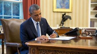 President Barack Obama signs an official document in the White House