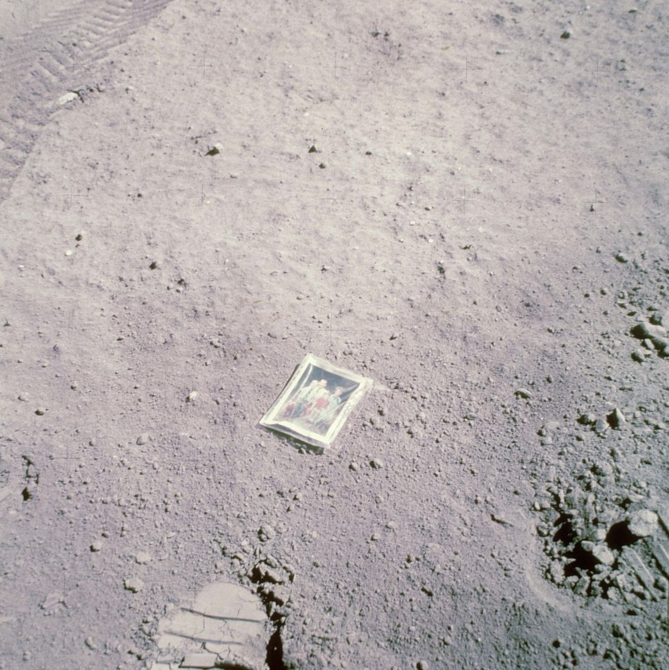 Astronaut Charles Moss Duke, Jr. leaves a photograph of his family on the surface of the moon during the Apollo 16 lunar land
