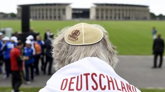 A member of the German Team wears a kippa as he sits at the so-called 'Maifeld', a place used by Nazis for mass rallies, near the Olympic Stadium of Berlin where a Memorial ceremony for the victims of the Holocaust is to be held before the official opening ceremony of the 14th European Maccabi Games in Berlin, on July 28, 2015. The Maccabi games dubbed the Jewish Olympics bring together more than 2,000 athletes at the site of the 1936 'Nazi Games'.    AFP PHOTO / TOBIAS SCHWARZ        (Photo credit should read TOBIAS SCHWARZ/AFP/Getty Images)