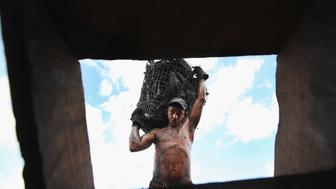 RONDON DO PARA, BRAZIL - JUNE 08: A worker carries a bag of charcoal produced from illegally harvested Amazon rainforest wood up a ladder onto a truck on June 8, 2012 in Rondon do Para, Brazil. According to a recent Greenpeace study, illegal wood charcoal is primarily used in Brazil to power smelters producing pig iron, which is used to make steel for industries including U.S. auto manufacturing. Illegal charcoal camps were found to sometimes result in slave labor and the destruction of rainforest on protected indigenous lands. Between 2003-2011, 2,700 charcoal camp workers were liberated from conditions akin to slavery, according to Greenpeace.  The worker in this photo said he was paid $40 per truckload of charcoal.  The Brazilian Amazon, home to 60 percent of the world's largest forest and 20 percent of the Earth's oxygen, remains threatened by the rapid development of the country. The area is currently populated by over 20 million people and is challenged by deforestation, agriculture, mining, a governmental dam building spree, illegal land speculation including the occupation of forest reserves and indigenous land and other issues. Over 100 heads of state and tens of thousands of participants and protesters will descend on Rio de Janeiro, Brazil, later this month for the Rio+20 United Nations Conference on Sustainable Development or 'Earth Summit'. Host Brazil is caught up in its own dilemma between accelerated growth and environmental preservation. The summit aims to overcome years of deadlock over environmental concerns and marks the 20th anniversary of the landmark Earth Summit in Rio in 1992, which delivered the Climate Convention and a host of other promises. Brazil is now the world's sixth largest economy and is set to host the 2014 World Cup and 2016 Summer Olympics.  (Photo by Mario Tama/Getty Images)