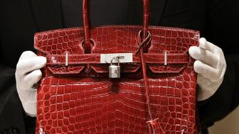 A employee holds a 129,000 USD crocodile Hermes Birkin Bag for the press to see during a private opening for the new Hermes store on Wall Street in New York 21 June 2007. The store which is located at 15 Broad Steet is across the street from the New York Stock Exchange. The store is one of several luxury shops opening near Ground Zero as part of a revitalization project in the area.  AFP PHOTO/ TIMOTHY A.  CLARY        (Photo credit should read TIMOTHY A. CLARY/AFP/Getty Images)