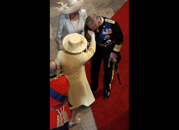 Prince Charles kisses the hand of his mother, Queen Elizabeth, before his son's wedding ceremony.   (AFP photo)