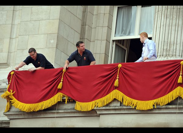 Staff dress the balcony at Buckingham Palace ahead of the royal wedding. (Getty photo)