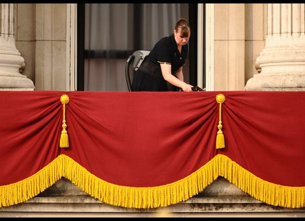 A worker makes the final preparations on the balcony of Buckingham Palace.   (Getty photo)