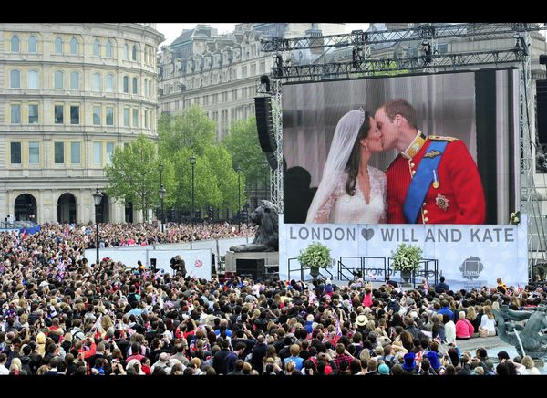 Fans watch Prince William and Kate kissing on a giant screen in Trafalgar Square in central London.  (Getty photo)