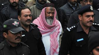 This photograph taken on December 22, 2014, shows Pakistani police escorting the head of banned Lashkar-e-Jhangvi (LeJ) Malik Ishaq as he arrives at the high court in Lahore. The leader of a banned Pakistani sectarian militant group is set to walk free from jail, officials said on December 23, even as the government considers 'radical changes' to tackle militancy after a Taliban school massacre. Malik Ishaq, the head of Lashkar-e-Jhangvi (LeJ), which is dedicated to killing minority Shiite Muslims, is expected to be released on Thursday after the Punjab provincial government withdrew a request to extend his detention under public order laws. AFP PHOTO/STR        (Photo credit should read STR/AFP/Getty Images)
