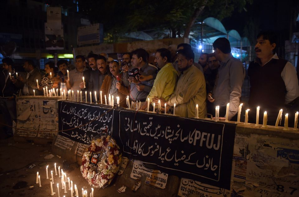 Pakistani journalists light candles for the victims of an attack by Taliban gunmen on a school in Peshawar, in Karachi on Dec