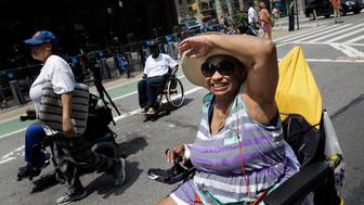 Jeanette Gaston dances to music in the inaugural Disability Pride Parade, Sunday, July 12, 2015, in New York. The parade grand marshal was former U.S. Sen. Tom Harkin, the Iowa Democrat who 25 years ago sponsored the Americans With Disabilities Act. (AP Photo/Seth Wenig)
