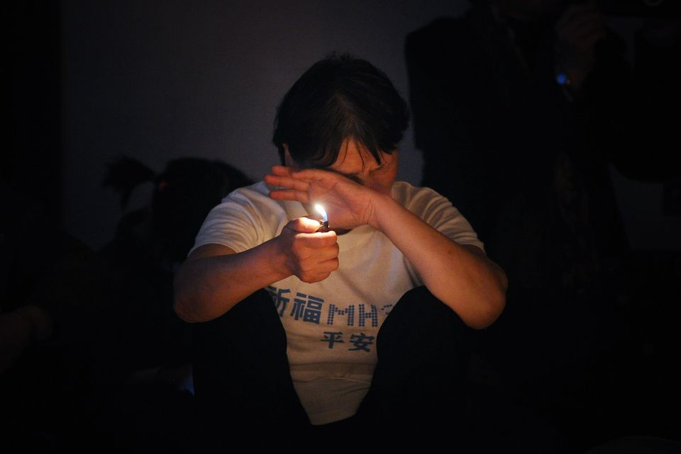 A Chinese relative of passengers on the missing Malaysia Airlines flight MH370 uses a lighter as she prays at the Metro Park