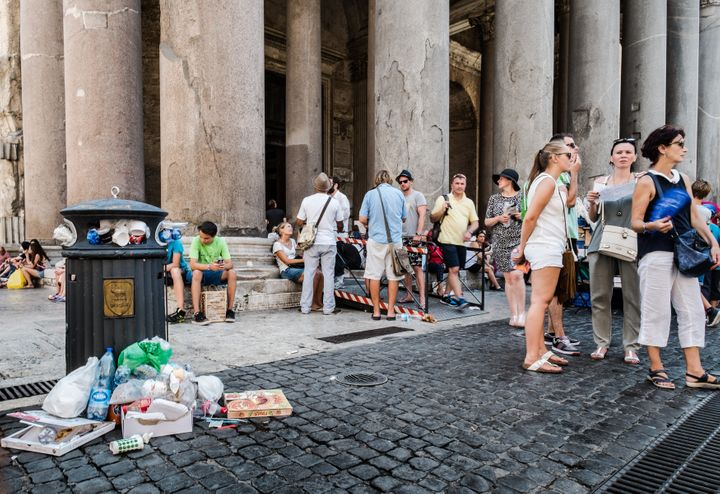 <span>Tourists stand next to a bin overflowing with waste in front of the Ancient Pantheon, in central Rome on July 27, 2015.