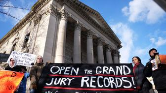 Protesters display a banner and placards during a demonstration outside the courthouse in New York's borough of Staten Island on January 5, 2015, before a hearing in a state lawsuit seeking the release of grand jury proceedings concerning the death of Eric Garner. Garner, a father of six who was suspected of illegally selling cigarettes, was wrestled to the ground by several white police officers after resisting arrest on Staten Island on July 17, 2014. Classified as a homicide by the New York medical examiner's office, his death set off intense reactions and several protests in New York reminiscent of those in Ferguson, Missouri, over the August 9 police shooting of unarmed black teenager Michael Brown. AFP PHOTO/JEWEL SAMAD        (Photo credit should read JEWEL SAMAD/AFP/Getty Images)