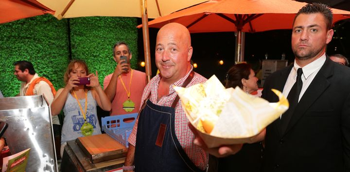 Food writer Andrew Zimmern, left, with someone who probably hasn't tried donkey before.