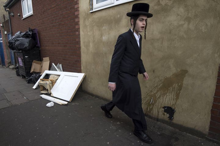 An Orthodox Jewish man walks past a damaged door belonging to the Ahavas Torah synagogue in the Stamford Hill following a sus