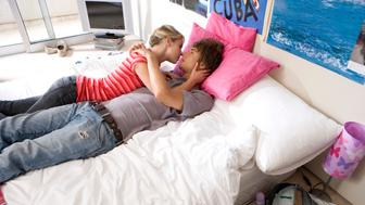 Teenage couple (15-17) kissing on bed, elevated view