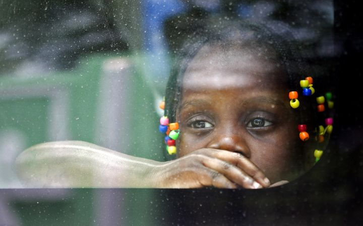 <span><span><span>A Haitian girl looks from the window of a vehicle as her family is transported to be voluntarily