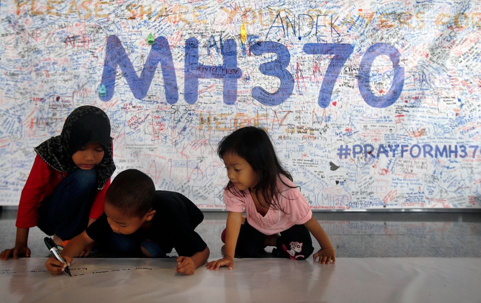 Young children write messages on a 60-meter long banner filled with signatures and well wishes for all involved with the miss