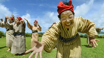 TO GO WITH AFP STORY BY ALASTAIR HIMMER In this picture taken on June 22, 2015, an elderly women troupe of singers and dancers from Kohama Island in Okinawa wearing traditional local costumes perform at a herb garden on Kohama Island, Okinawa Prefecture. They joke about knocking on heaven's door, but a Japanese 'girl band' named KBG84, with an average age of 84 have struck a blow for grannies everywhere by becoming pop idols. AFP PHOTO / Toru YAMANAKA        (Photo credit should read TORU YAMANAKA/AFP/Getty Images)
