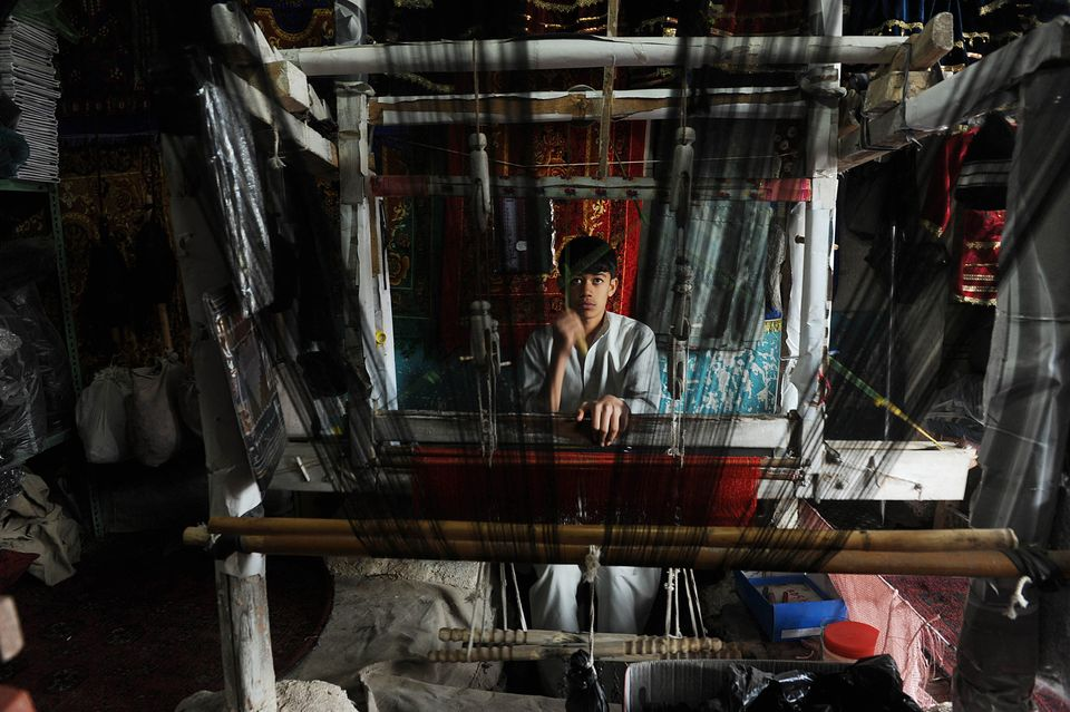 An Afghan worker weaves a silk shawl in Herat on November 4, 2012. (Aref Karimi/AFP/Getty Images)