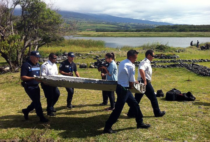 <span>Police carry a piece of debris from an unidentified aircraft found in the coastal area of Saint-Andre de la Reunion, in