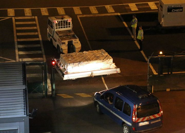 <span>&nbsp;Police officers escort an airport vehicle transporting what is believed to be debris from a Boeing 777 plane that