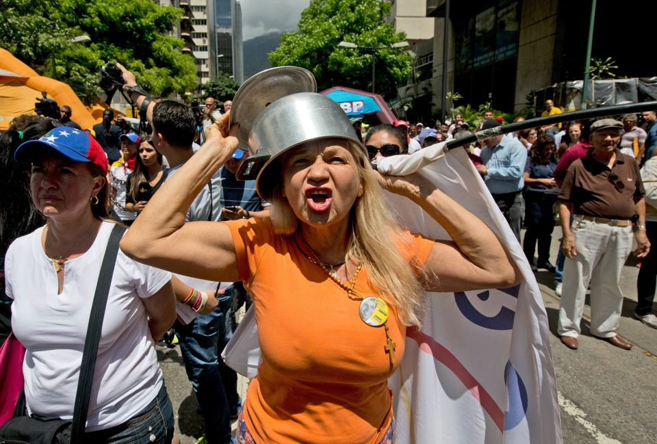 An opposition member wearing a pot on her head shouts slogans against Venezuela's President Nicolas Maduro during a protest i