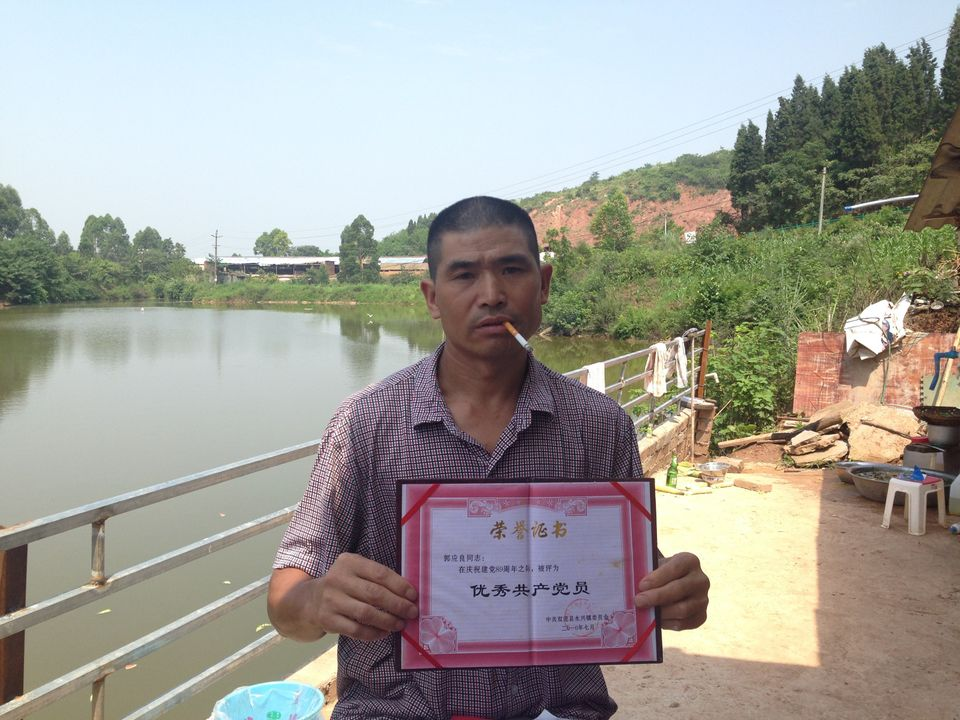 "Guo Yingliang, a farmer who has protested over compensation on his seized farmland, holds up a certificate commending him as an ""Excellent Communist Party Member."" Three days after this photo was taken his wife, Wu Ping, was reportedly detained."