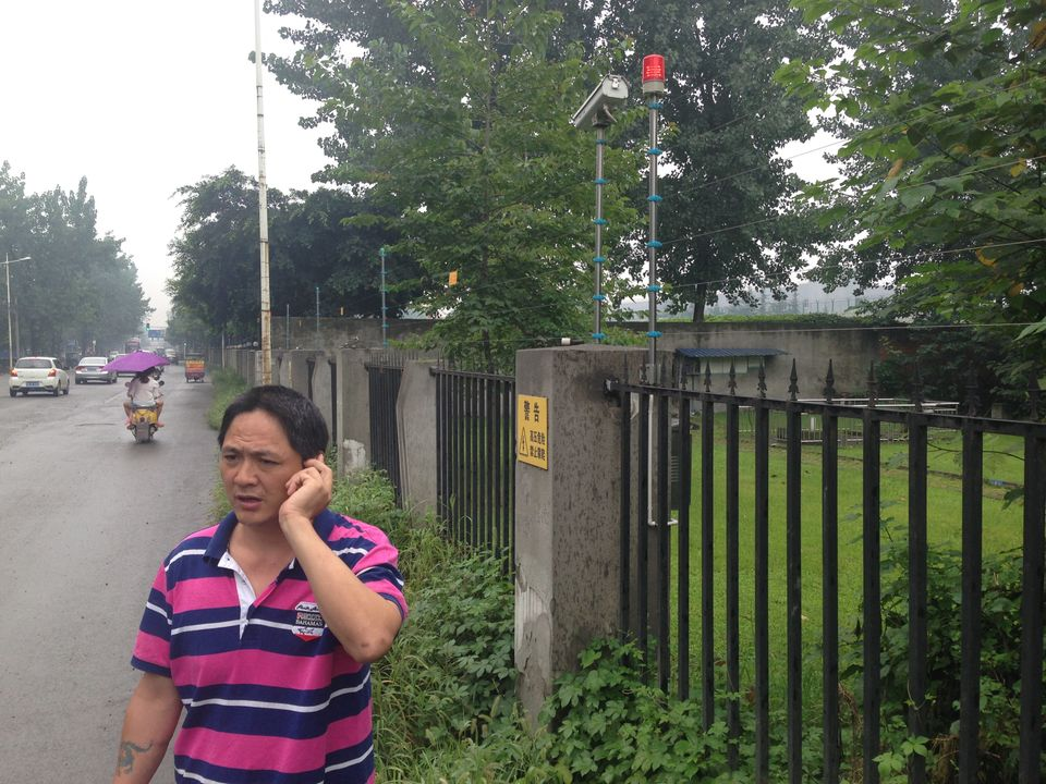 "Liu Zhizhong searches his wife, Li Ming, outside a prison on July 20th. Li was detained on July 18th and remains in custody on charges of ""obstructing official duties."""