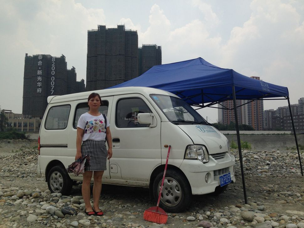 Yuan Ying stands beside the car that she uses to block construction on the site of her former home.