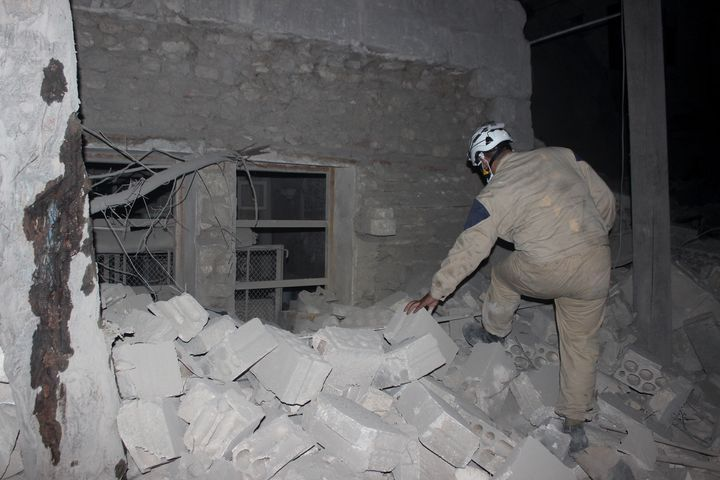 A search and rescue team member inspects the rubble after Assad forces barrel bomb attack to Aleppo, Syria, on August