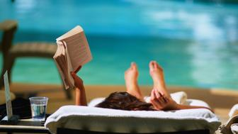 Woman reading by hotel swimming pool.