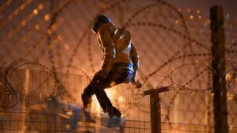 CALAIS, FRANCE - AUGUST 3 :  A migrants camped out in Calais, attempts to climb a security fence near refugee camp of Calais, France on August 3, 2015. More than 2 thousands migrants waiting at Calais forests, hoping to get to Britain, camp out in Calais, on August 3, 2015. (Photo by Mustafa Yalcin/Anadolu Agency/Getty Images)