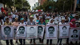 MEXICO CITY, MEXICO - JULY 26: Demonstrators and relatives of the 43 missing students of Ayotzinapa college march during a protest rally ten months after the 43 students disappearance on July 26,  2015 in Mexico City, Mexico. (Photo by Miguel Tovar/LatinContent/Getty Images)