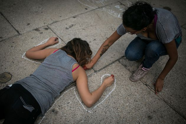 A woman paints the silhouette of a girl during a protest to demand the safe return of the 43 missing students of Ayotzinapa, on June 26, 2015 in Mexico City.