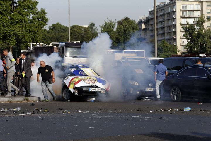 <span>Smoke rises as demonstrators light firecrackers at Porte Maillot in Paris on June 25, 2015, as hundreds of taxi drivers