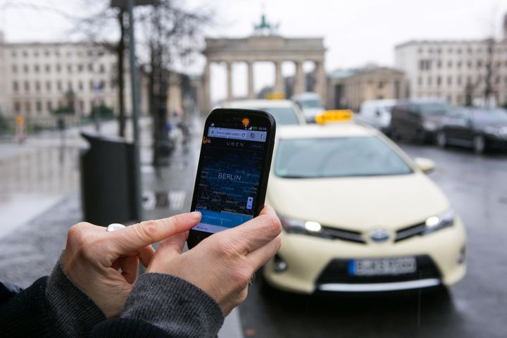 <span>A smartphone displays the Uber app in this arranged photograph as taxis and the Brandenburg Gate stand beyond in Berlin