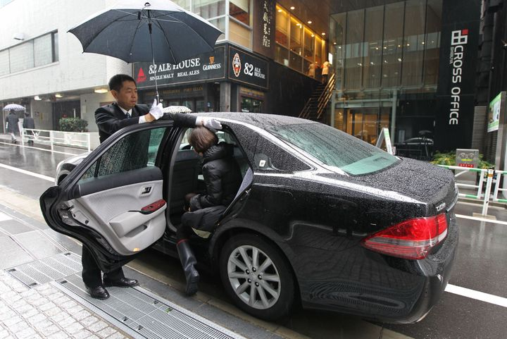 <span>A driver opens the door for a customer during a demonstration outside the Uber Japan Co. office in Tokyo, Japan, on Wed