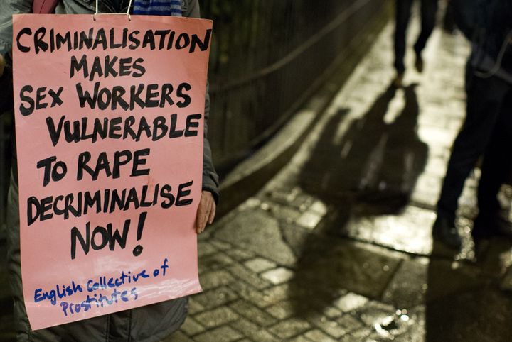 A protester holds a placard on the international day to end violence against sex workers, organized by the English Collective