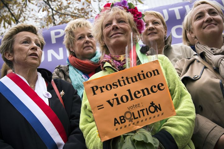 Former French sex worker Rosen Hicher (center), an activist for the abolition of prostitution, holds a placard at a Paris dem