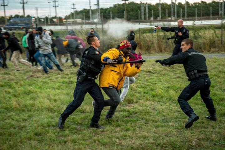 <span>French gendarmes try to stop migrants on the Eurotunnel site in Coquelles near Calais, northern France, on late July 29
