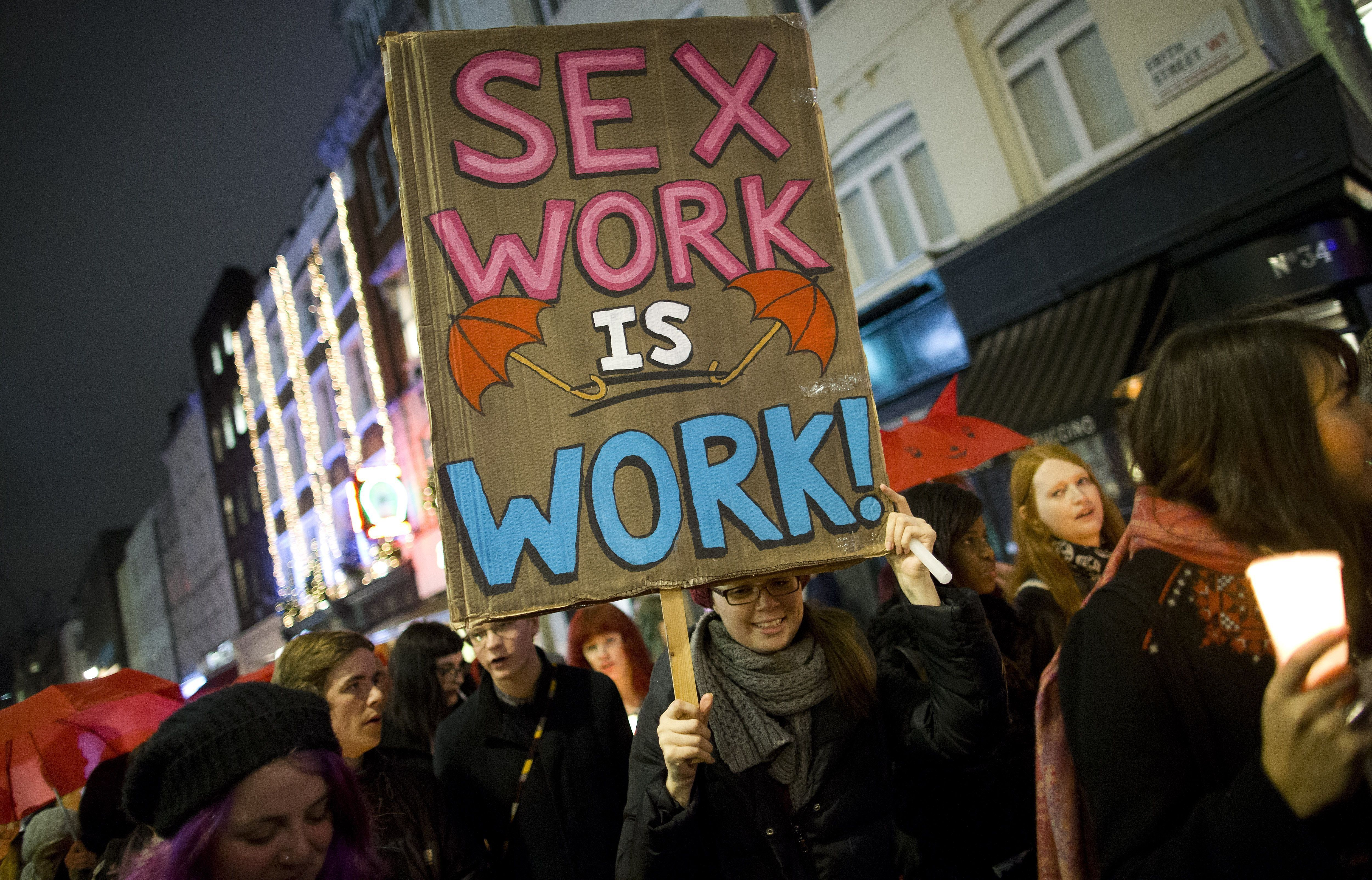 A protester holds a placard whilst marching through Soho after a candle-lit vigil to mark the international day to end violence against sex workers, organised by the English Collective of Prostitutes, in London on December 17, 2014. AFP PHOTO / JUSTIN TALLIS        (Photo credit should read JUSTIN TALLIS/AFP/Getty Images)