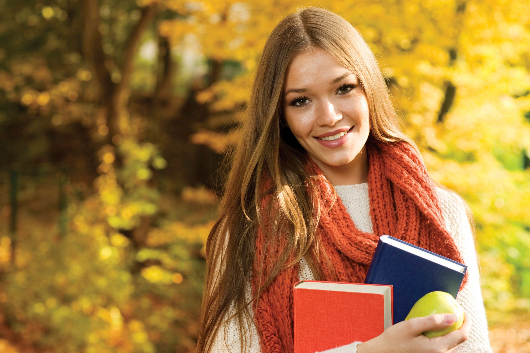 Young college girl with books smiling at camera