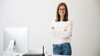 Portrait of a smiling businesswoman standing with arms folded in office