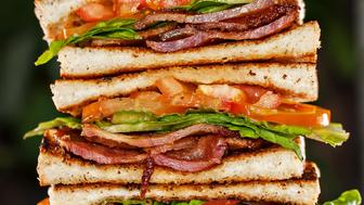 Sandwiches on a wooden chopping board. Thick cut bacon, fresh lettuce, and fresh tomatoes.