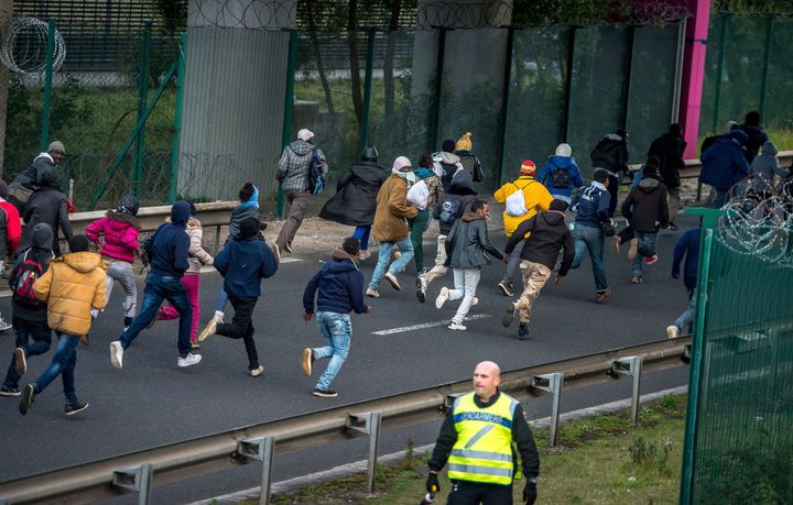 <span>Migrants trying to reach the Channel Tunnel run past a policeman on the Eurotunnel site in Coquelles near Calais, north