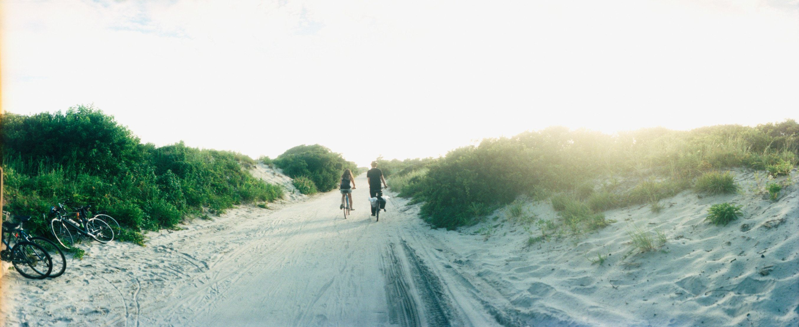 Rear view of a couple cycling along a beach trail, Fort Tilden, Queens, New York City, New York State, USA