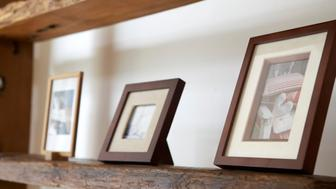 Framed photos on wooden shelf, close-up